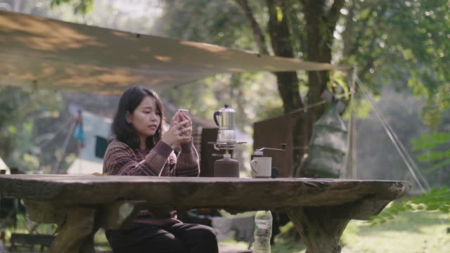 Female making coffee using hand and taking a picture of her Coffee maker with a smartphone on camping trip.