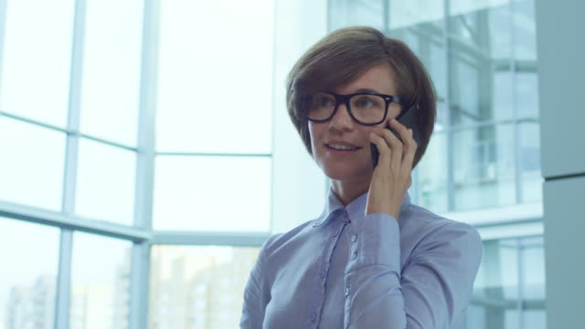 female manager in eyeglasses talking on cell phone - call center стоковые видео и кадры b-roll
