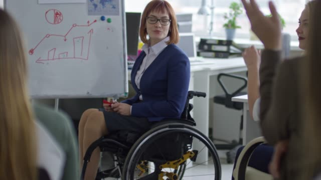 vídeos de stock e filmes b-roll de female manager in wheelchair leading business seminar - envolvimento dos funcionários