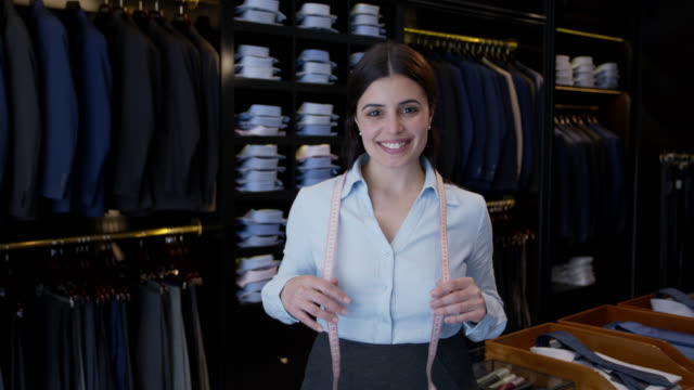 Female manager of a men's clothing store smiling at camera holding a tape measure around her neck Female manager of a men's clothing store smiling at camera holding a tape measure around her neck very cheerfully saleswoman stock videos & royalty-free footage