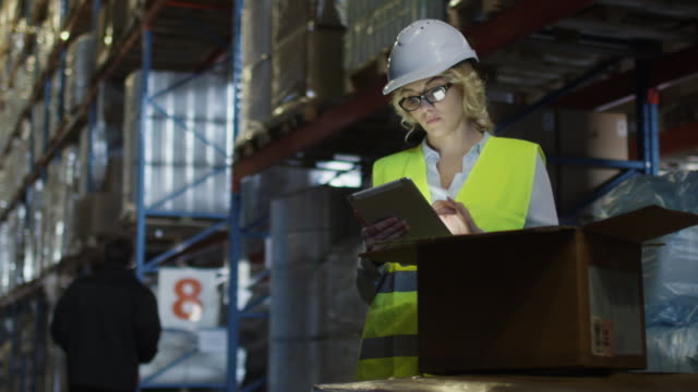 Female Manager of Logistics Warehouse is Working on Tablet PC. Wears a White Hard Hat. video