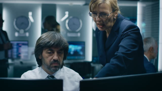female manager talks with professional operator working on a personal computer in the system monitoring room. high profile specialist working. - quartiere generale video stock e b–roll