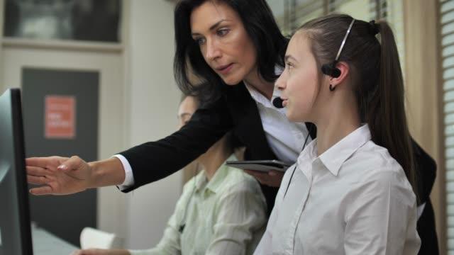 Telemarketer de entrenamiento mujer manager usa el receptor en el ordenador en la oficina - vídeo
