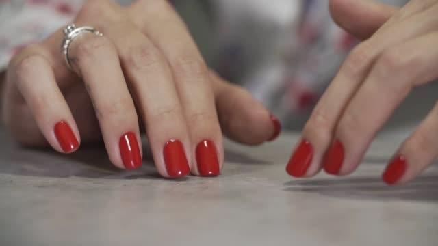 weibliche maniküre arm hautnah. nahaufnahme von frau finger mit roten nägeln - maniküre stock-videos und b-roll-filmmaterial