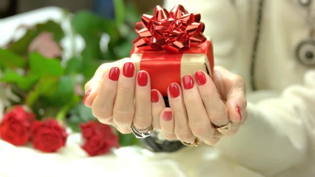 female manicured hands with gift box. - nastro per capelli video stock e b–roll