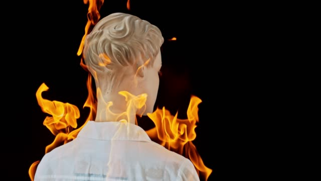 SLO MO LD Female mannequin in a white shirt catching fire
