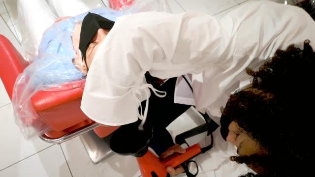 vídeos de stock e filmes b-roll de female masked hairdresser blow drying customer's hair at salon's reopening - covid hair