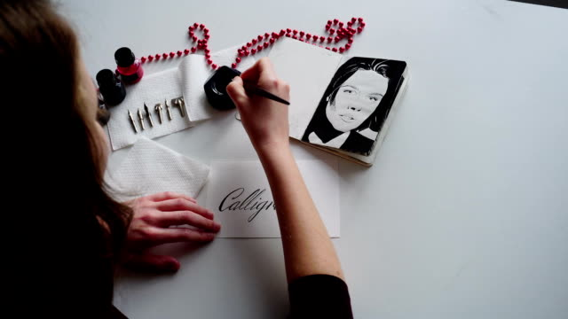 Female master of lettering of ink writes word on paper, sitting at table in studio