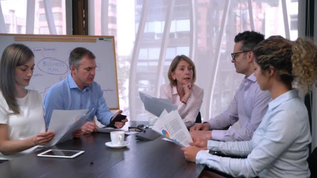vídeos y material grabado en eventos de stock de líder de negocios madura femenina asignando diferentes tareas a su equipo apuntando a cada uno y a la junta durante una reunión - zoom meeting
