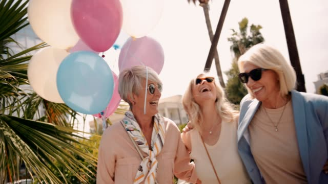 vídeos de stock e filmes b-roll de female mature friends having fun in the city with balloons - mulher balões