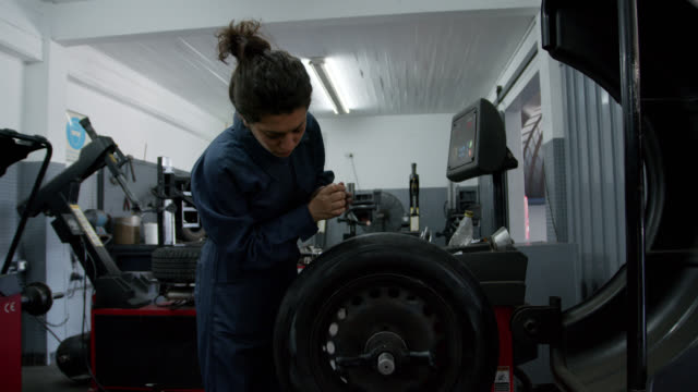 Female mechanic at a car garage checking the readings on machine repairing a wheel