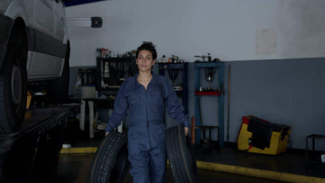 Female mechanic carrying tires at an auto repair shop