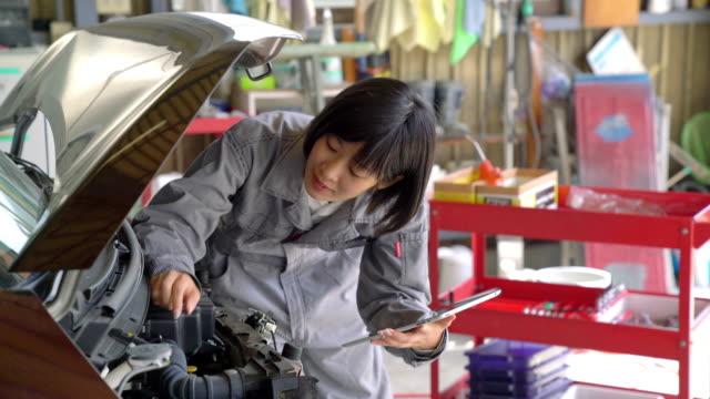 女性のメカニックが車のエンジンをチェック - 機械工点の映像素材/bロール