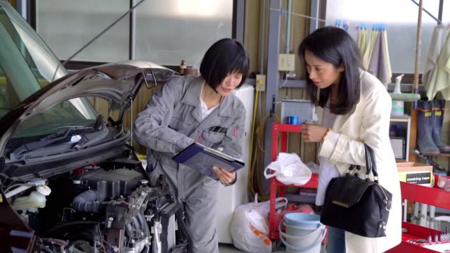 お客様に修理女性メカニックの説明 - 機械工点の映像素材/bロール