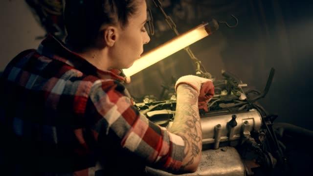 weibliche mechaniker in der werkstatt. befestigung motor - garage stock-videos und b-roll-filmmaterial