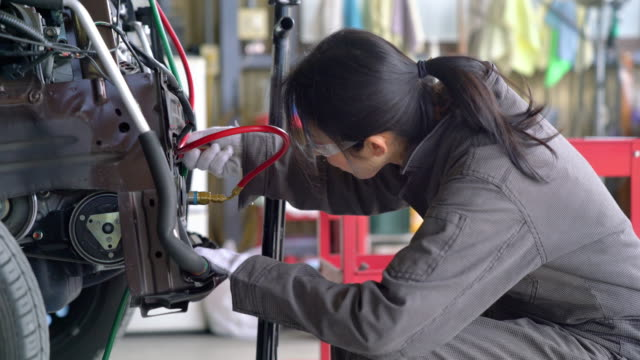 Female mechanic in her garage working on a car video