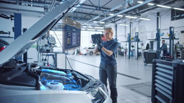 механик-женщина использует планшетный компьютер с программным обеспечением для диагностики дополненной реальности. специалист инспектир - моторное транспортное средство стоковые видео и кадры b-roll