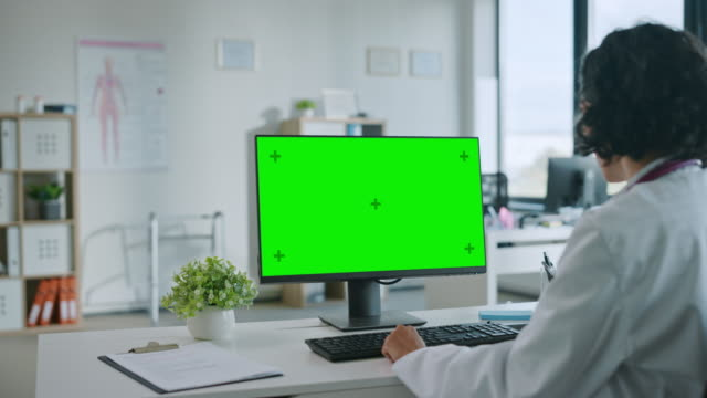Female Medical Doctor is Working on a Computer with Green Screen Mock Up Display in a Health Clinic. Assistant in White Lab Coat is Reading Medical History Behind a Desk in Hospital Office.