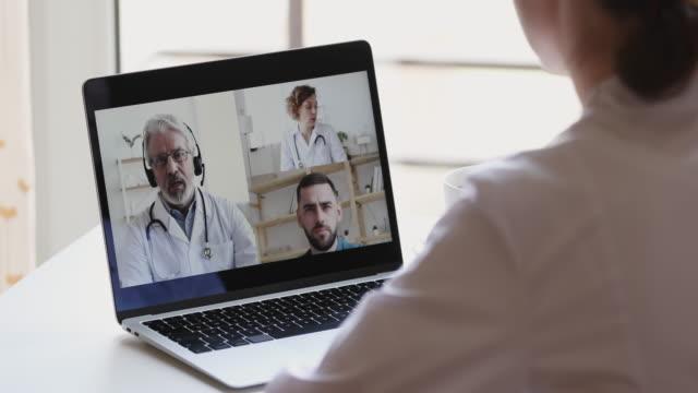 stockvideo's en b-roll-footage met vrouwelijke medische arbeider die online webcamconferentievraag op laptop deelneemt - corona scherm