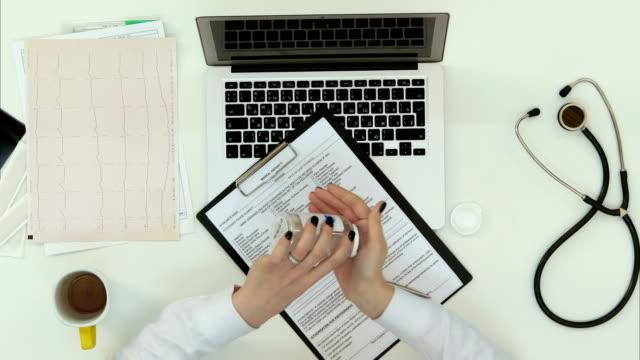 vidéos et rushes de travailleuse médical prescrivant des pilules via vidéoconférence - pots de bureau