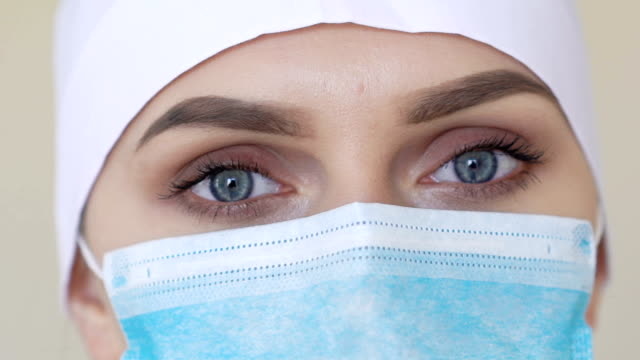 Female medical worker wearing face mask looking into camera video