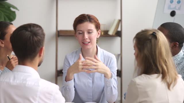 vídeos y material grabado en eventos de stock de mujer mentora que habla enseñando a diversos estudiantes internos en la reunión de grupo - consejero de la escuela