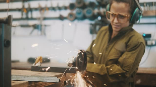 Female Metal worker using circular saw (slow motion)