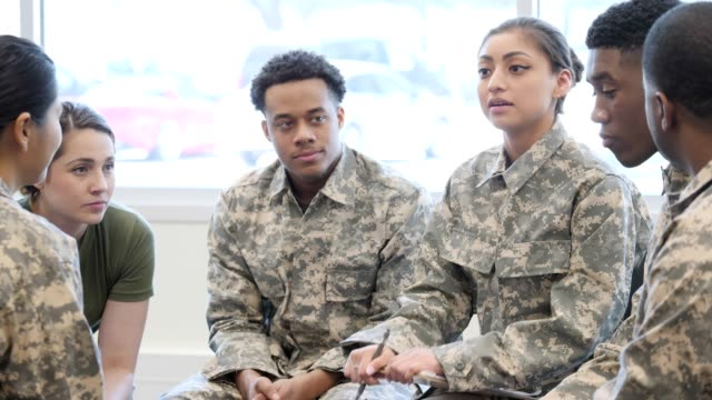 Female military counselor leads support group with soldiers Young female soldier gives instructions to a group of cadets or leads a support group for military veterans. She gestures while talking with a male soldier. She then turns her attention to the rest of the group. military uniform stock videos & royalty-free footage