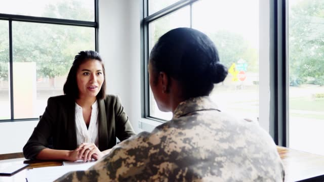 Female military soldier meets with counselor Caring female counselor listens and gives advice to a mid adult female soldier during the soldier's weekly counseling session. military lifestyle stock videos & royalty-free footage