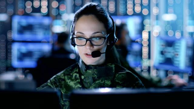 女性軍のテクニカル サポート担当者は、ヘッドセットに指示を与えます。彼女は多くの他の役員とモニター ルームで作業が表示されます。 - デイフェンス点の映像素材/bロール