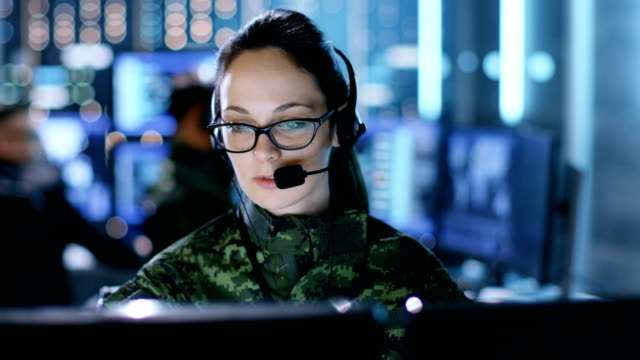 Female Military Technical Support Professional Gives Instructions into Headset. She's in a Monitoring Room with Other Officers and Many Working Displays. video
