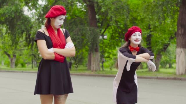 female mimes play scenes in the park - гримировальные краски стоковые видео и кадры b-roll