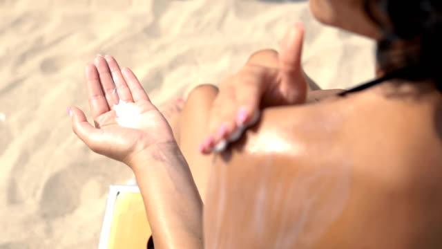 vídeos de stock e filmes b-roll de female model apply sunblock cream on hand and shoulder, sitting on beach, cinematic dof - protetor solar