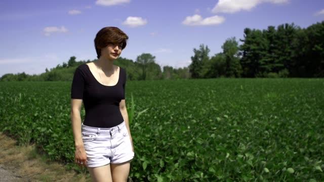 Female model walking in field Female model walking in field wearing pink dress and boots. daylight savings stock videos & royalty-free footage
