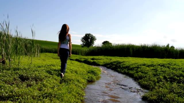 Modelo feminino caminhada do rio gramado campo ecologia fundo de viagem - vídeo