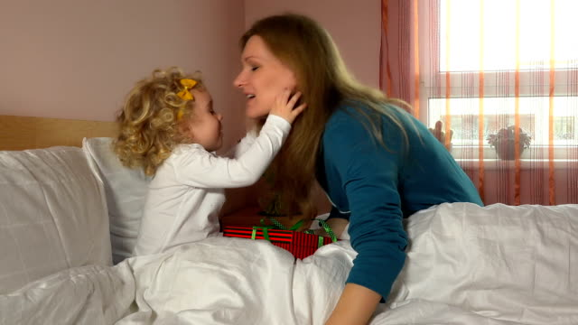 Female mother kiss daughter child and give present gift box