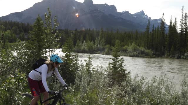 weibliche mountainbikerin folgt pfad in der nähe des flussrandes - eskapismus stock-videos und b-roll-filmmaterial
