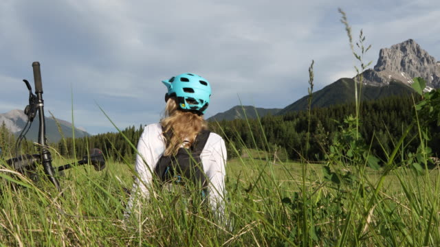 female mountain biker relaxes in mountain meadow - эскапизм стоковые видео и кадры b-roll