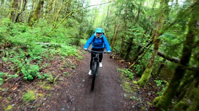 vídeos de stock e filmes b-roll de female mountain biker rides along forested path - 55 59 anos