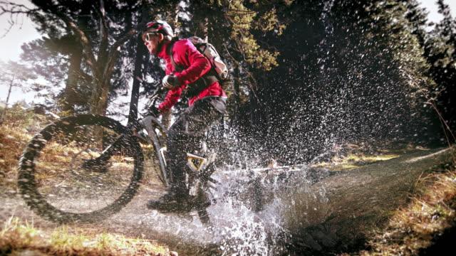 hizli rampa orman su birikintisi ile sürme kadın dağ bisikletçisi - sadece genç bir kadın stok videoları ve detay görüntü çekimi