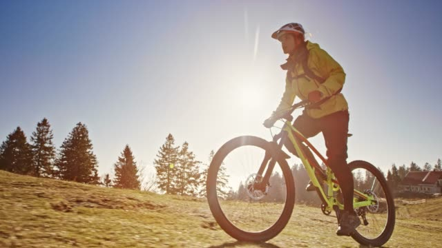 SLO MO TS Female mountain biker riding up the mountain meadow in sunshine Slow motion wide low angle tracking shot of a female mountain biker riding up the sunny mountain meadow. Shot in Slovenia. biking stock videos & royalty-free footage