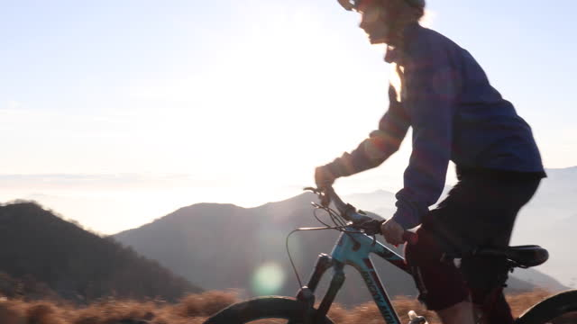 mountain biker femmina attraversa sentiero alpino, vicino vetta - percorso per bicicletta video stock e b–roll
