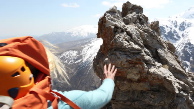 female mountaineer ascends rock pinnacle above mountains - leanincollection stock videos & royalty-free footage