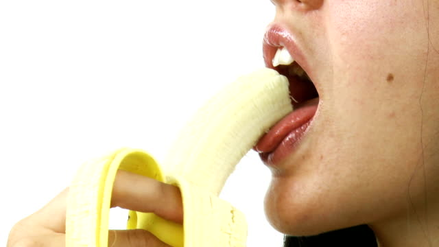 Female mouth eating peeled banana video