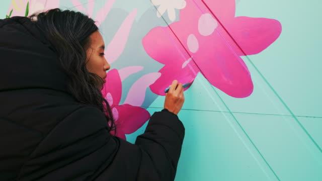kvinnlig väggmålningskonstnär på jobbet - väggmålning bildbanksvideor och videomaterial från bakom kulisserna