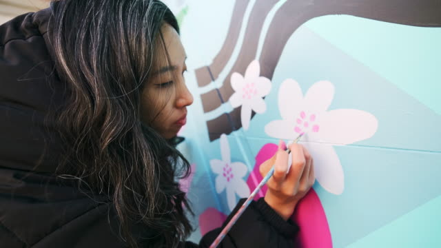 Female mural artist at work Female mural artist creating art on the garage door of the private home in the city. mural stock videos & royalty-free footage