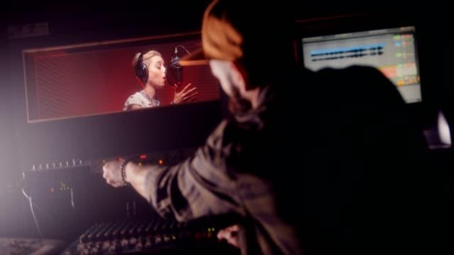 kadın müzik sanatçı ve müzik stüdyosunda kayıt müzik yapımcısı - kulaklık seti ses ekipmanı stok videoları ve detay görüntü çekimi