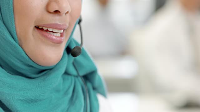 TU Female Muslim call center operator taking a call video