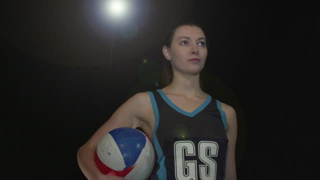 Female Netball Player Portrait pose - Super Slow Motion 180 degree rotation Stock HD video clip footage of a female netball Player. Filmed in Super Slow motion, the camera rotates 180 degrees around the player. Black Background. Indoors pre game stock videos & royalty-free footage
