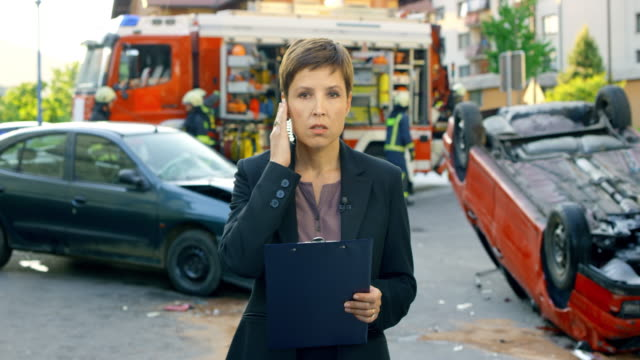 Female news reporter reporting live from the scene of a car accident Wide handheld shot of a female reporter reporting live from the scene of a car accident. Shot in Slovenia. journalist stock videos & royalty-free footage